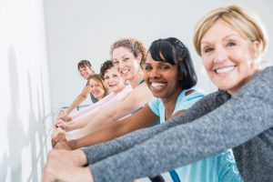 Multi-ethnic group of women (30s to 60s) in exercise class. Main focus on woman 3rd from right.