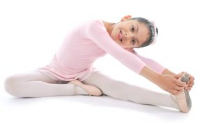 young cute Ballerina girl stretching legs wearing pink Ballet tutu isolated on a white background